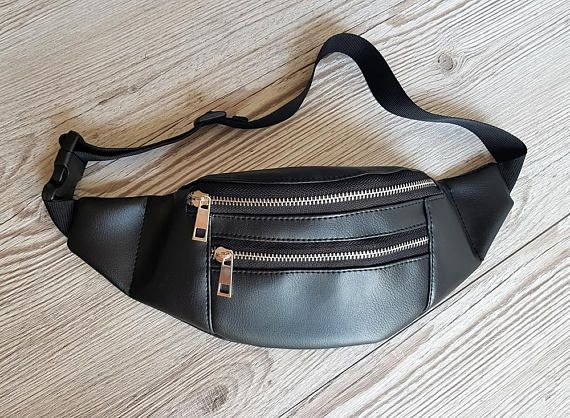 Simple and stylish black fanny pack made of high quality vegan (faux) leather. Great for travelling, walking, camping and any occasion when you need to look cool and have a free hands.   Bag has metal zipper closure and small zippered pocket on the front.  All the using parts of the bag are double or triple stitched. The bag is fully lined. Lining is made of sturdy waterproof fabric so you can be sure that the bag is super sturdy upside and inside and will last a long time.   Dimensions…