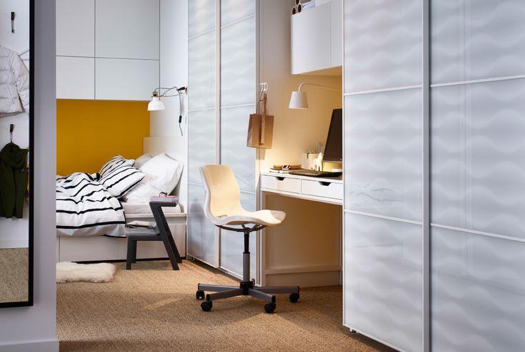 Pohled na oblast kolem postele, šatní skříně IKEA a pracovní plochu