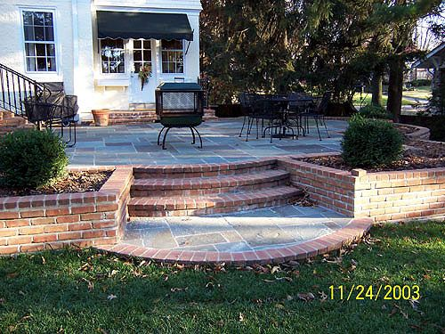 Pennsylvania blue stone patio with brick steps and planter for Brick wall patio designs