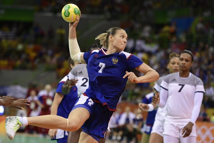 Russia's centre back Daria Dmitrieva (L) jumps to shoot past France's left back Allison Pineau (R) during the women's Gold Medal handball match France vs Russia for the Rio 2016 Olympics Games at the Future Arena in Rio on August 20, 2016. / AFP / afp / JAVIER SORIANO