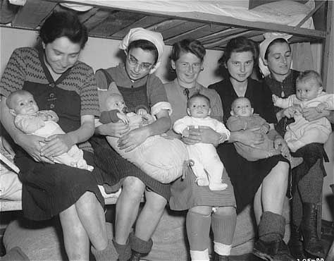 Shown from left to right in the photo above are: Iboyla Kovacs with her daughter Agnes; Suri Hirsch with her son Yossi; Eva Schwartz with her daughter Maria; Magda with her daughter; and Boeszi Legmann with her son Gyuri. These Hungarian women survived Dachau with their babies.