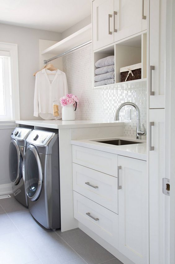 Laundry Room Organization Ideas. Folding Counter. Mud Room Sink. Glass Tile Backsplash. White Built-in Cabinets. Drying Rack.