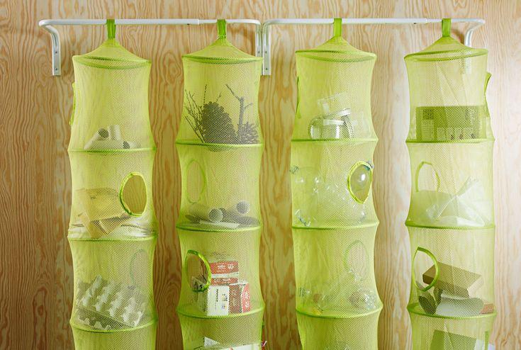 Cuatro cestos de almacenaje colgantes hechos con malla verde con materiales para reciclar en su interior.