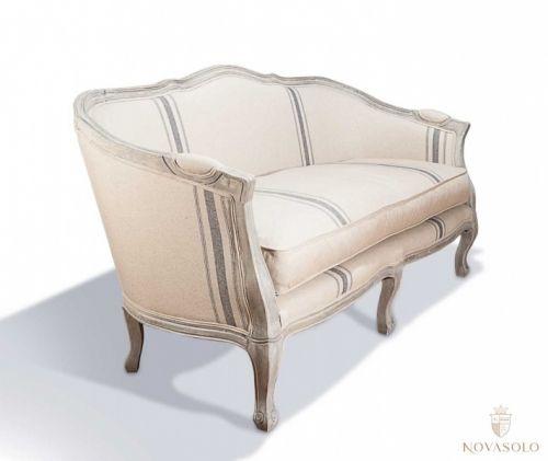 Lekker, delikat og innbydende Country sofa. Dette er en mindre sofa for deg som har like stort behov for en dekorativ sofa som sittteplasser. Sofaen har gråvasket rammeverk i solid eik med påkostede utskjæringer samt et pent sandfarget stoff med nedtonede blå striper - en liten perle!