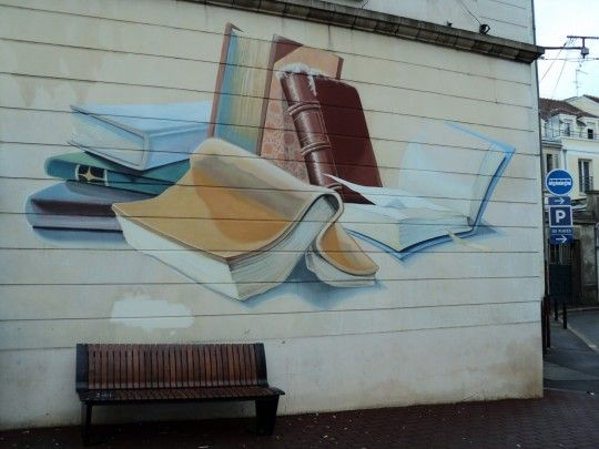 Street art - La Bibliotheque: La Bibliothèque. A small mural on a library building in small town near Fontainebleau, France. Pictured by Kelly Robic.