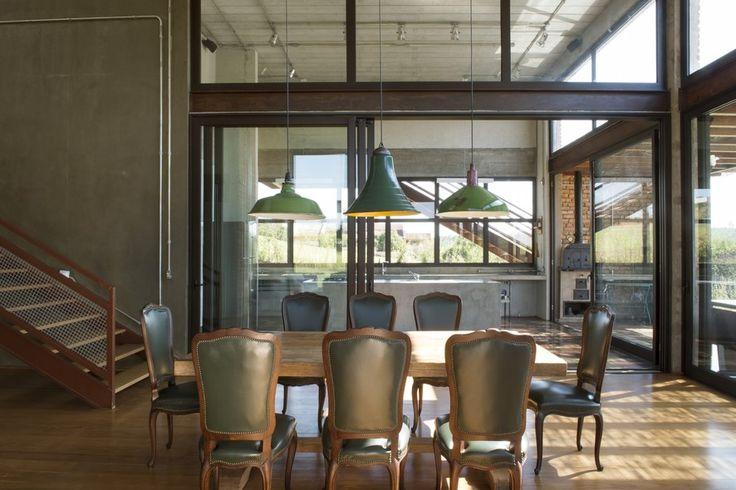 Integrada à cozinha por painéis de vidro em caixilhos metálicos deslizantes, a sala de jantar tem mesa e cadeiras de antiquário. Pendentes industriais, da Forja Recicla, conversam com as tubulações elétricas aparentes. Projeto do Estúdio Vitor Penha