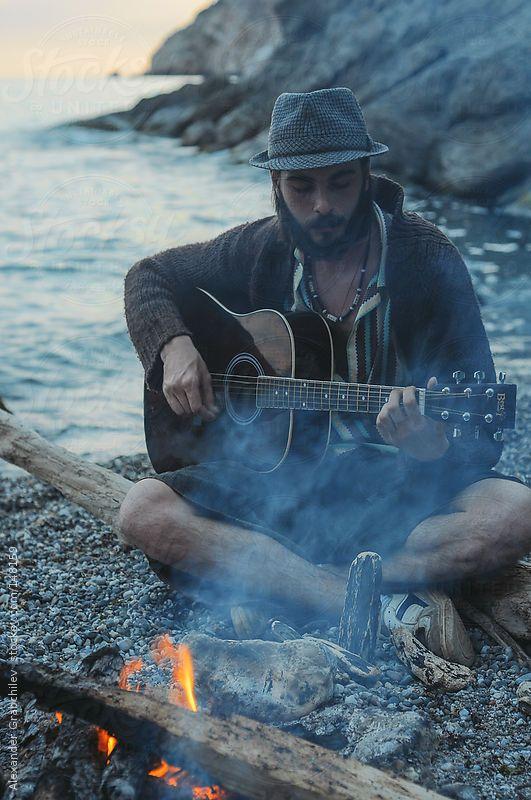 gypsy guy playing guitar near campfire on the beach, Crimea, Ukraine