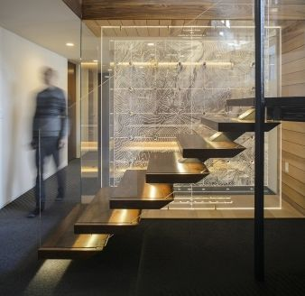 A wood staircase with floating glass balustrade connects the two levels
