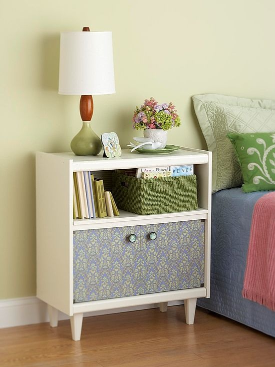 White nightstand with pattern doors. This is made from one of those old rolling TV carts everyone used to have. Take the casters off and replace with wooden legs, paint, change door handles, and cover doors with wall paper or paint and stencil. Makes a great night stand! Hm...I think we have one of these in the basement.