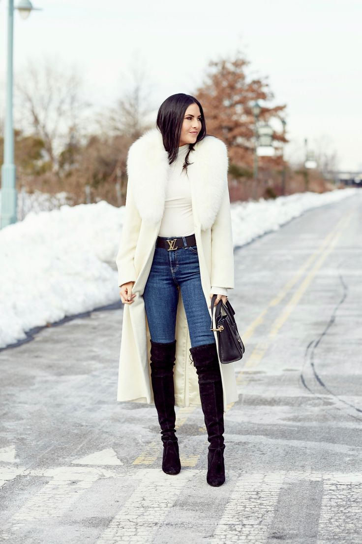 A white faux fur coat can be worn over anything! She paired it with jeans, a white top and over-the-knee boots: perfection!