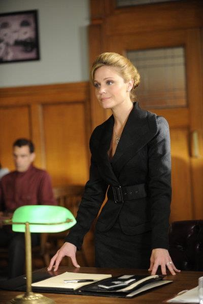 Season 1 Episode #7 - Coming Home . . . . . . . . ~Lauren Outfit 3) Black wool skirt suit with large lapel collar and large belt , diamond encrusted circular pendent necklace and pearl stud earrings - Defending Sofia Pena in immigration court
