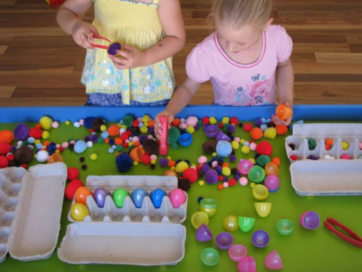 empty egg cartons, tweezers, coloured pompoms and plastic eggs ,The sensory table became a bit of a factory with sorting, making, moving, creating, role playing, pretending and games.  Using the tweezers, put pompoms into the plastic eggs and place them into egg cartons. They made a game where they had to guess what color pompom was inside the egg. Use the tweezers to sort the pompoms into color groups in the egg cartons.  They also made a rainbow pattern by sorting the pompoms.