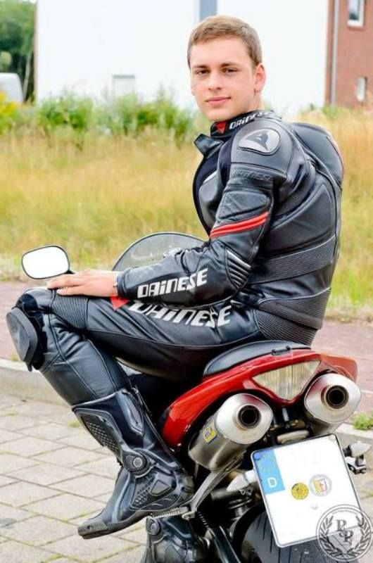 young biker in shiny leather gear