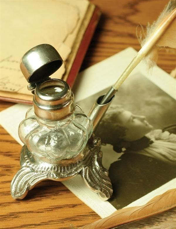 """Antique Reproduction Pewter Glass Inkwell with Quill Pen. Anyone will write more pensive prose using this beautiful set. The 3"""" inkwell is of bubble glass shape with pewter base, cap and quill holder and measures 3"""". The authentic quill color will vary. Please allow 1 week for order processing. $19.50"""