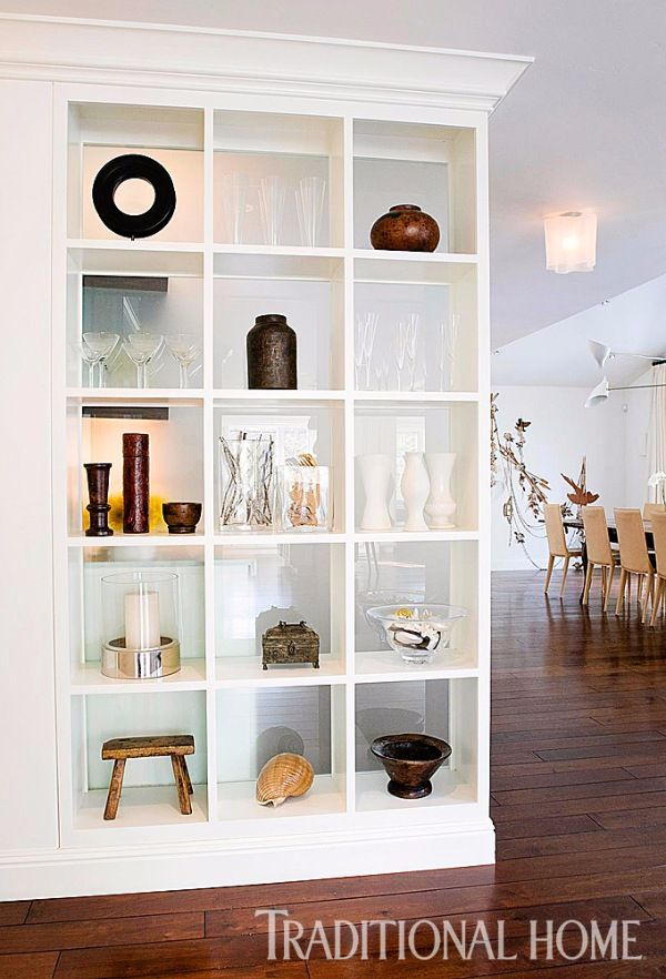 A custom-made bookcase, backed with opaque glass, divides the entryway from the dining area. On display is an array of objects—ranging from pottery by Eva Zeisel to pieces from Thailand and Bali. - Photo: Angie Silvy / Design: Kriste Michelini