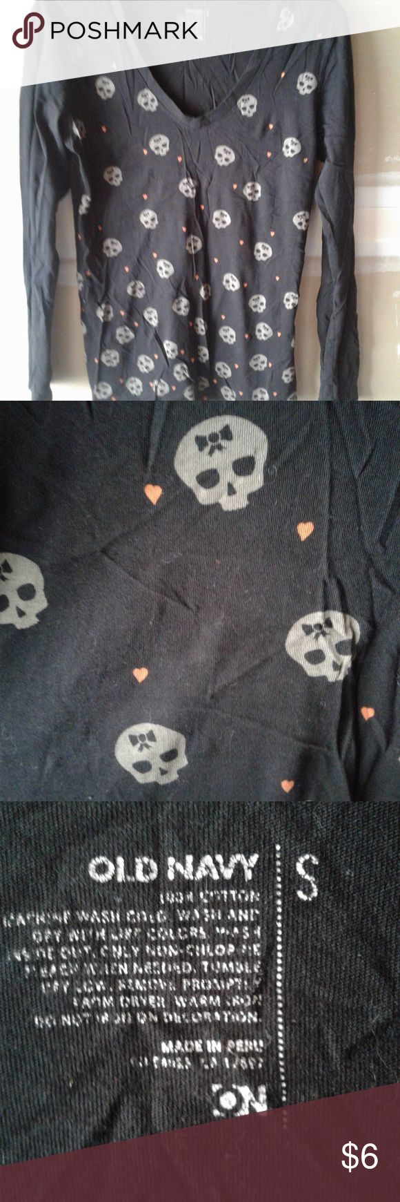 Skulls and bows This is a pretty, soft, super comfy shirt. It can be used around Holloween or all year around. The skulls have little bows on their head and theres little orange hearts.  It should not be this wrinkled when recieved Old Navy Tops Tees - Long Sleeve
