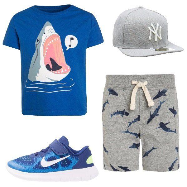Total look comodo per bambino composto da una t-shirt in cotone blu con uno squalo stampato, un paio di pantaloncini grigi di cotone con elastico in vita e piccoli squali stampati, un berretto con visiera in grigio e un paio di sneakers multicolore.