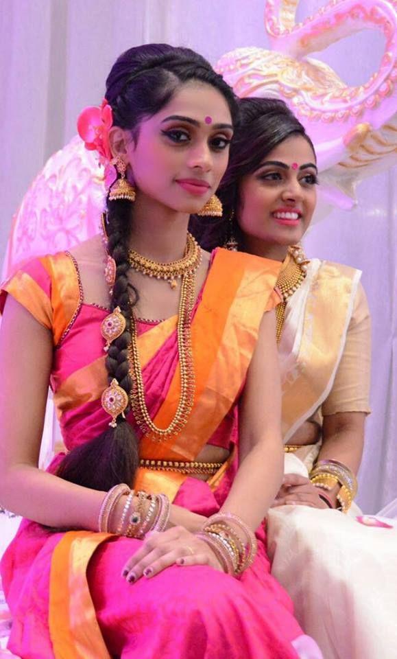 South Indian bride. Gold Indian bridal jewelry.Temple jewelry. Jhumkis.pink and orange silk kanchipuram sari.Braid with fresh flowers. Tamil bride. Telugu bride. Kannada bride. Hindu bride. Malayalee bride.Kerala bride.South Indian wedding.