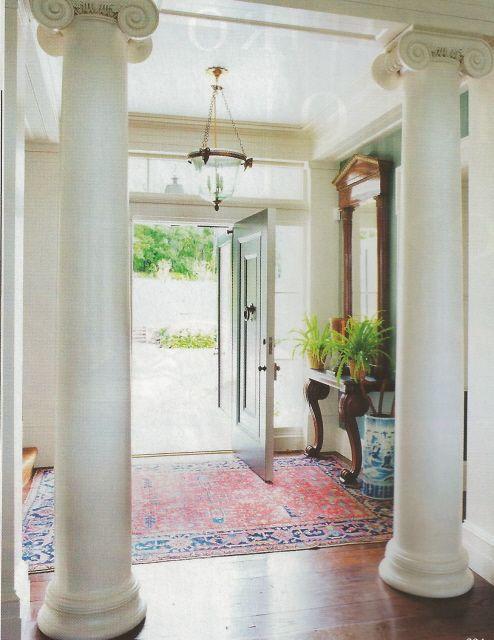 Classic entry - oversize columns, blue and white umbrella stand, antique rug, ferns, black door - November 2010 Veranda: Gil Schafer, Architect; Miles Redd, Interior Design
