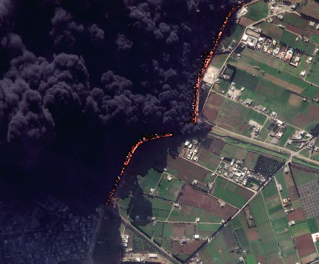 """This satellite image shows a pipeline fire in Homs, Syria. The pipeline, which runs through the rebel-held neighbourhood of Baba Amr, had been shelled by regime troops for the previous 12 days, according to two activist groups, the Local Coordination Committees and the Britain-based Syrian Observatory for Human Rights. The state news agency, SANA, blamed """"armed terrorists"""" for the pipeline attack."""