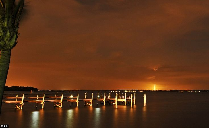 The SpaceX Falcon 9 launch appears in the distance from the back of River Rocks dockside r...