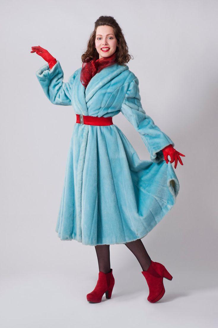 Lichtblauwe lange mantel van namaakbont, royaal klokkend uitlopend.