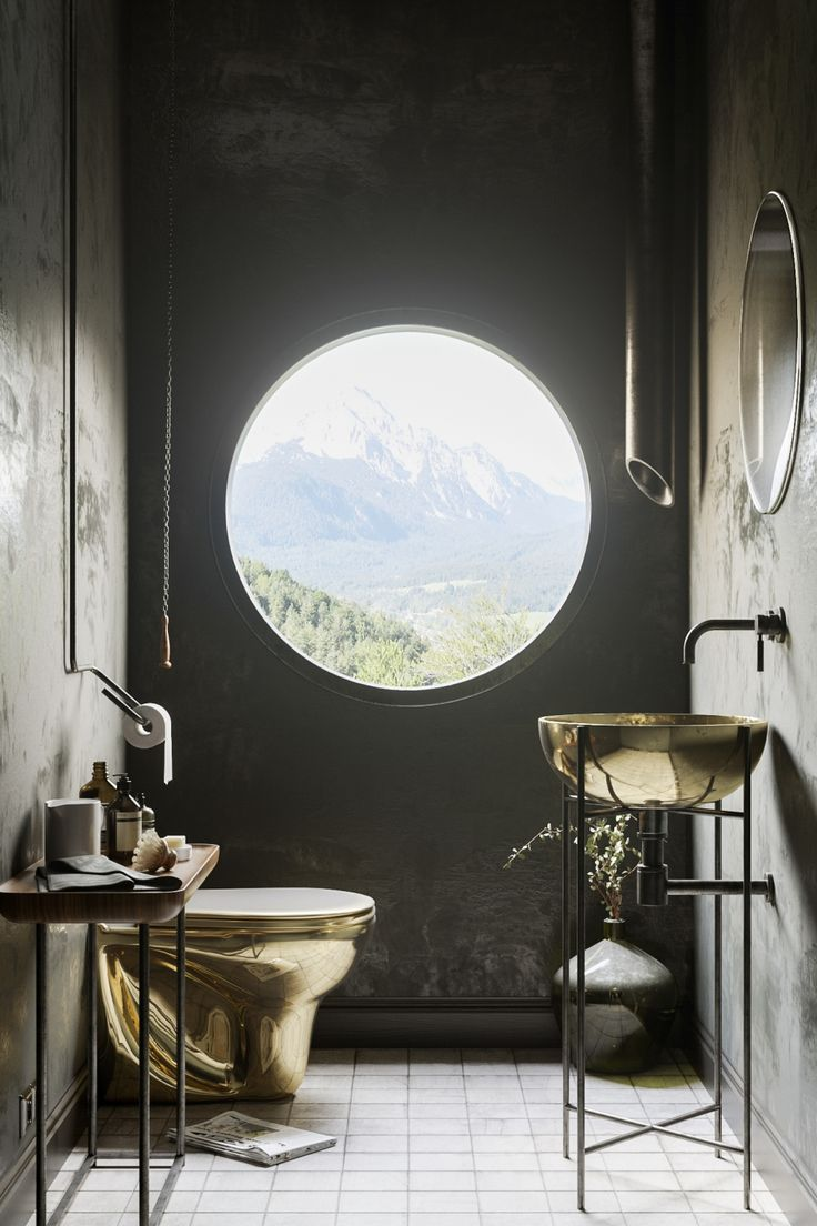 Gold bathroom suite with a round window looking over the mountains! Certainly a pretty unique bathroom.
