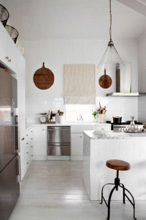 Vintage European timber chopping boards and mango wood stools from Orson & Blake add warmth to the all-white...