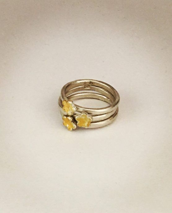Made by Sally Herbert. Small, beautifully simple and feminine textured Daisy stacking rings in Silver and Gold. Buy one or buy many to stack together.  Each ring is handmade and unique with a one-off gold overlay and texture on each daisy flower. Silver satin finish  This ring is made to measure.