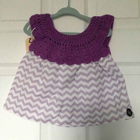 12-18 month size handmade baby girl dress with crochet top in purple cotton/nylon/polyester blend yarn with white & purple chevron pattern cotton fabric skirt, fastened at the back with a button. Lightweight and pulls over the head.