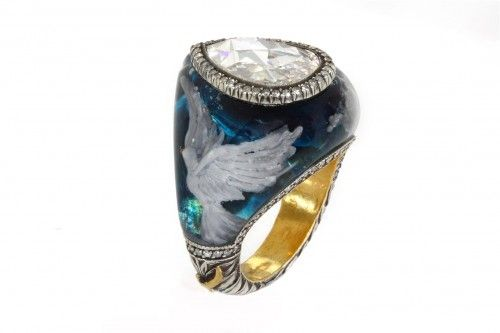 Sevan Bicakci Ring with a bird in wing in a blue sky surrounding a center diamond solitaire.