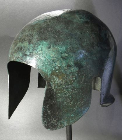 Corinthian helmet, early 6th century B.C.  Bronze helmet originally of Corinthian type, but modified in antiquity to a hybrid Illyro-Chalcidian type. The cheek pieces were cut away and the nose guard removed.  Openings for the ears were also added, 20.5 cm Private collectionsm from Artemis gallery