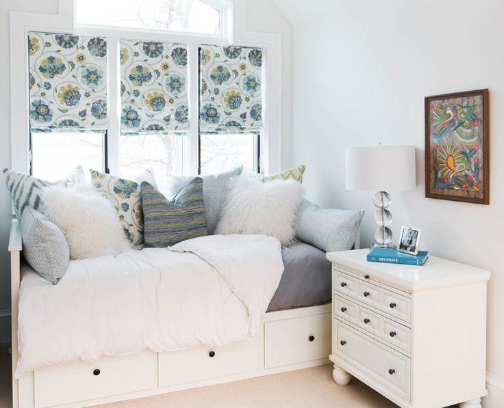 stores romains petit format en blanc et à motifs amusants, lit avec rangements et coussins décoratifs dans la chambre d'enfant blanche