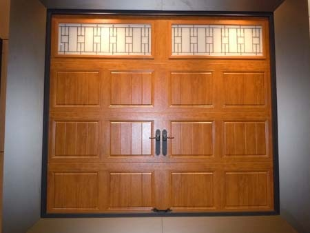 Clopay Gallery Collection grooved panel steel garage door. Medium Oak Ultra-Grain finish. Trenton windows.