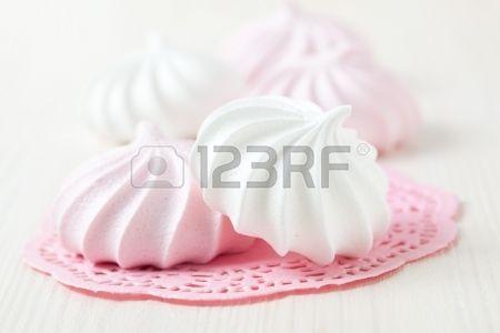 Blancos y rosados merengues descansando en rosa alfombrilla decorativa sobre fondo claro Foto de archivo