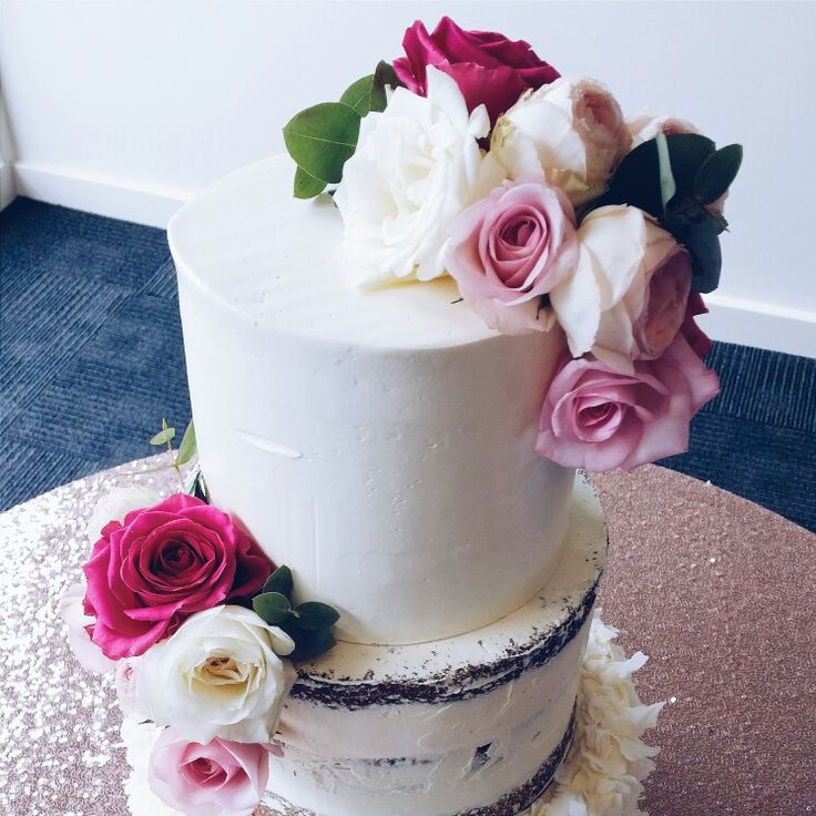 3 tiered textured white wedding cake. Bottom tier coconut flakes, middle tier naked cake with different toned white & pink roses