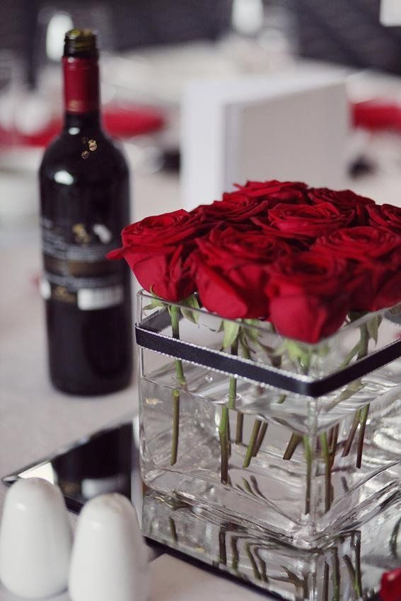 Table centre pieces: red roses in square vase with black ribbon