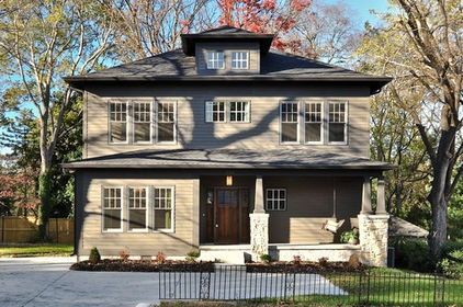 Partial-width front porches are a common exterior characteristic of American foursquare homes. This Nashville residence also features Craftsman characteristics such as stone pedestals, a three-panel front door and square-tapered columns.