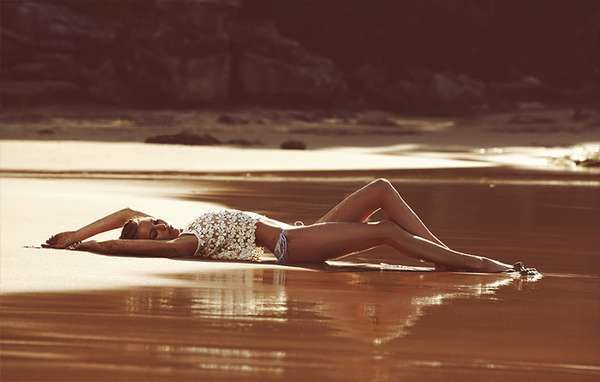 Lying arched on sand/water