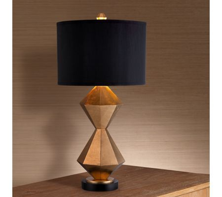 Complement any contemporary styled space with this modern gold table lamp. The sharp corners and faceted edges of the double stacked diamond design sit atop a round base. Topped with a black drum lamp shade to complete the look.