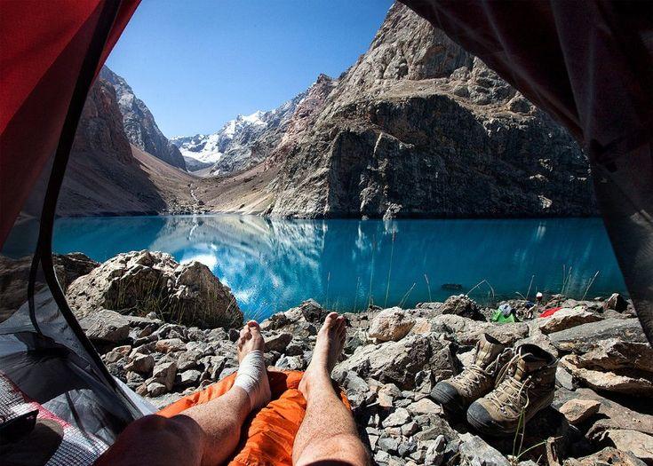 Füße vor dem Big Allo See in Tadschikistan: Zelten kann ganz schön ungemütlich sein - die Socken miefen, der Schlafsack kratzt, und man spürt den Boden unter der Luftmatratze, weil diese ein Loch hat. Doch es gibt diesen Moment beim Camping, der einen für alle Unannehmlichkeiten entschädigt: Wenn man morgens aufwacht, aus dem Zelt schaut, und einen wunderschönen Blick in die Natur hat.