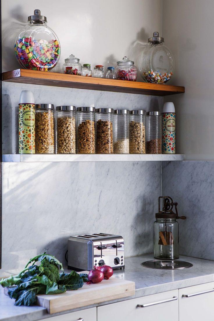 Cocina de una casa en Talar con una combinación de estanterías a la vista blancas y de madera. Además, frascos de diversos tamaños para almacenar alimentos.