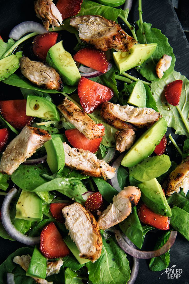A grilled chicken summer salad made with creamy avocado and sweet sliced strawberries.