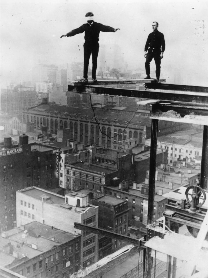 An American construction worker walking blindfolded on a construction girder twenty stories high in New York City, 1925.