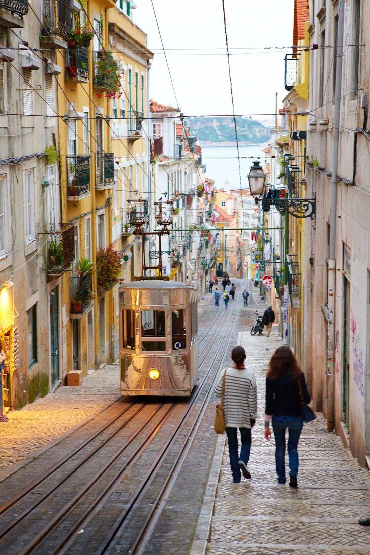 Elevador da Bica funicular on a steep cobbled street in Lisbon.