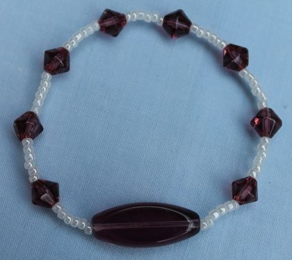 "This bracelet has a large purple transparent oblong bead with smaller purple bicone beads. In between the purple beads are white pearl seed beads. All threaded onto elastic. 21cm (8½"").  Materials used: Glass and elastic.   Nickel free."