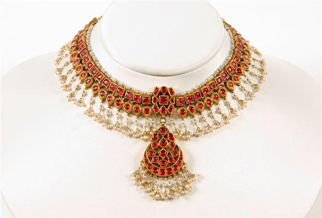 A gold necklace set with rubies and decorated with suspended pearls