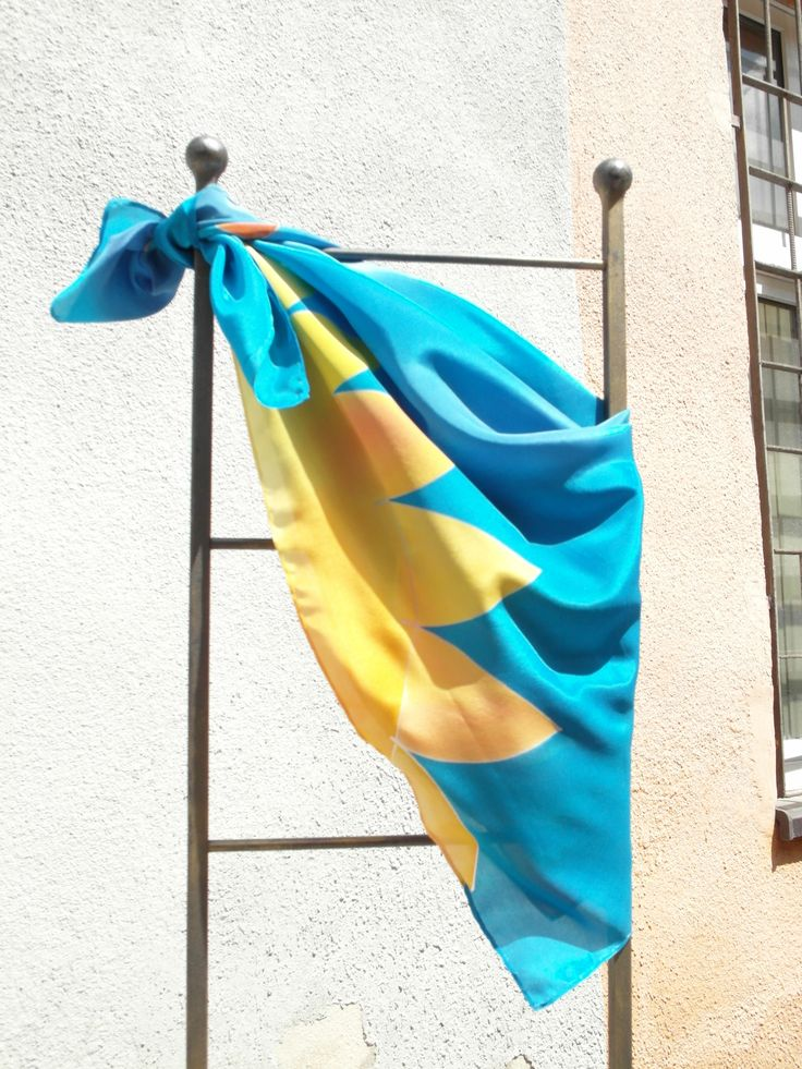 Turquoise blue silk pareo with yellow sun displayed on iron rack. Hand painted by SilkAgathe.