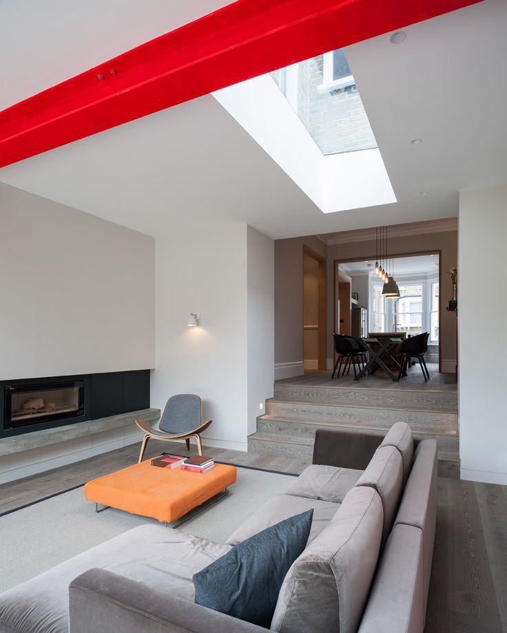 Beams supporting the rear extension of this Victorian house in west London are painted vivid red to create a bold contrast with the property's traditional interior