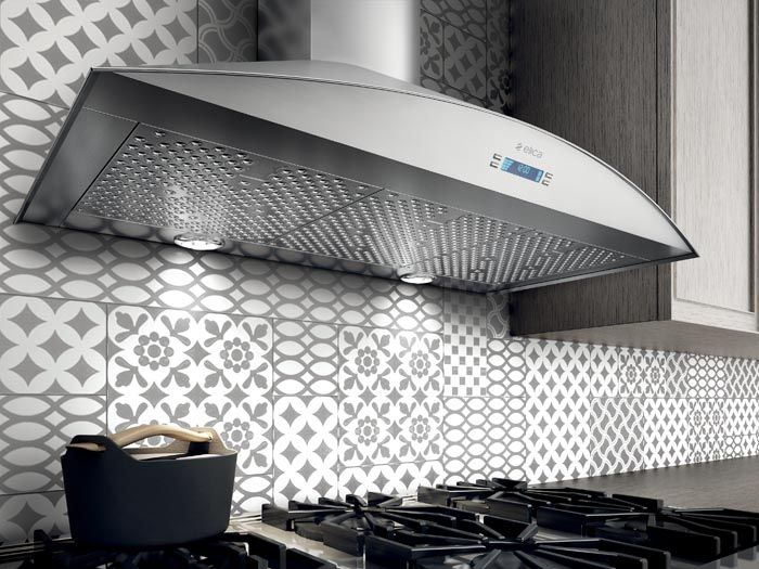 FOGLIA hood features a gently arched front that softens the unit's profile and…